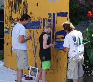 Local residents work on a Group of Seven mural.
